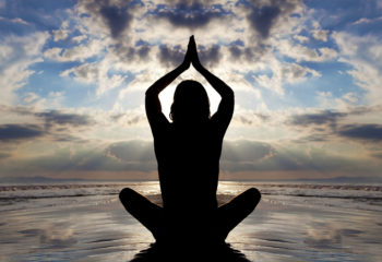 Silhouette beach yoga pose. Seated lotus.