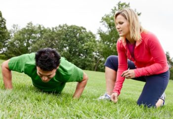 man-doing-push-ups-on-grass-near-woman